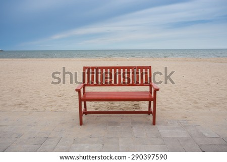 Alone wooden red beach chair sitting on the sand with sea. - stock photo