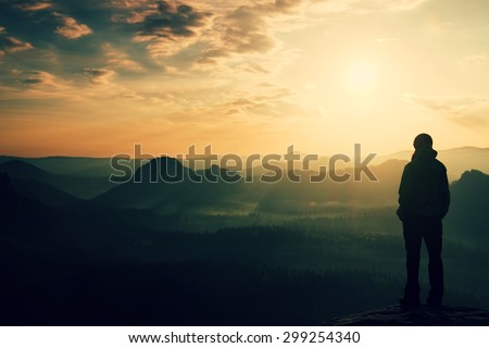 Alone young girl tourist feast daybreak on the sharp corner of sandstone rock and watch over valley to Sun. - stock photo