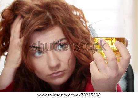 Alone young woman in depression, drinking alcohol (bourbon) - stock photo