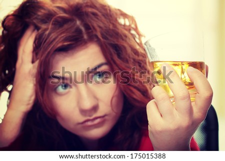 Alone young woman in depression, drinking alcohol (burbon) - stock photo