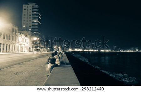 Along the Malecon, Havana, Cuba, people blurred in long exposure out at night in warm sea air sitting on sea wall across from the colonial buildings with the more modern city lights in distance. - stock photo