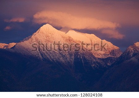 Alpenglow on the Mission Mountains in Montana.  Rocky Mountain Alpen Glow snow capped mountain peak summit - stock photo
