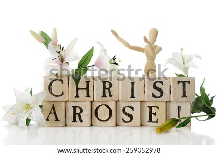 """Alphabet blocks arranged to say, """"Christ Arose!"""" surrounded by Easter lilies and a wooden mannequin with arms upraised in praise.  Isolated on white. - stock photo"""
