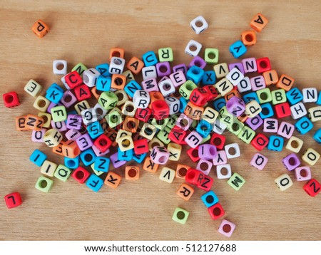 Alphabet in print on small plastic cubes and placed randomly on wood grain background.