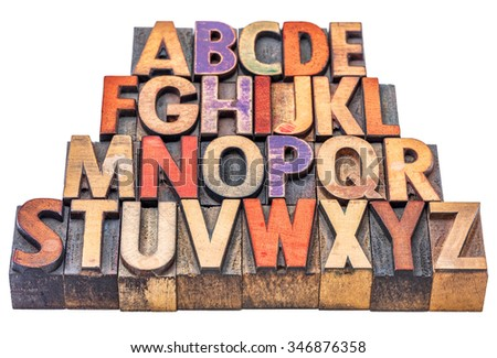 alphabet in vintage letterpress wood type stained by color inks,  isolated on white