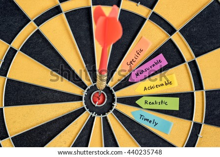 Alphabet letters hand writing words smart goals specific measurable achievable realistic timely with dart target arrow in bullseye on dartboard, Business success concept, Abstract background - stock photo