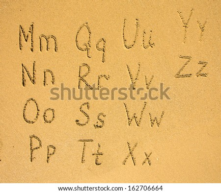 Alphabet (M-Z) written on a sand beach.  - stock photo
