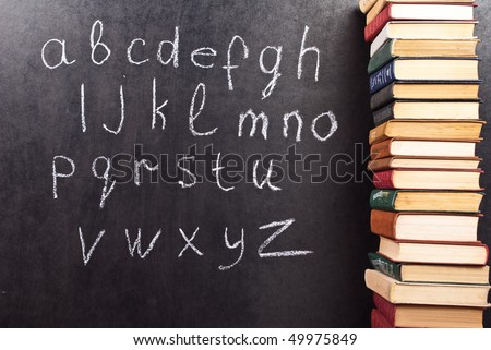 Alphabet on a chalkboard with books - stock photo