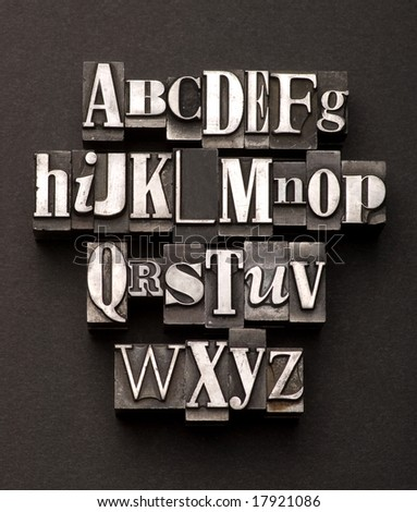 Alphabet photographed using a mix of vintage letterpress characters on a black, textured background.