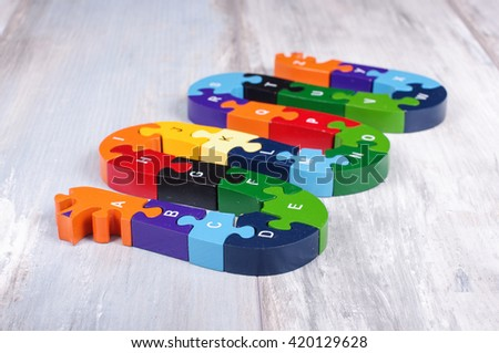 Alphabet snake puzzle game on the reclaimed oak surface - stock photo