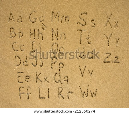 Alphabet written on a wet beach sand. - stock photo