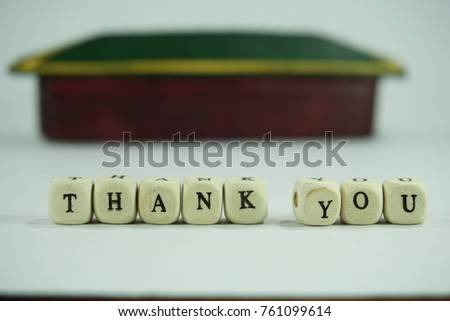 Alphabetical cube showing word of THANK YOU, isolated on white background. Selective focused using daily objects such as colorful items.