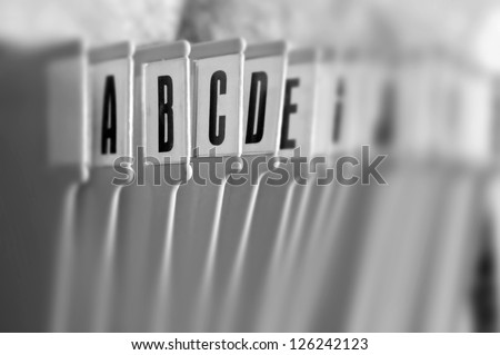 Alphabetical filing tray office index organizer. Selective focus black and white.