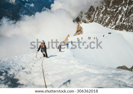 Alpine ascent on Aiguille du Midi mountain in french alps, chamonix. Group of people climbing the mountain, making extreme ascent, going through difficulties - stock photo
