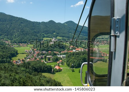 Alpine Cable Car Descends from a Mountain Peak on a Summer Day