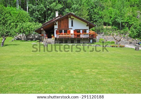 Alpine chalet in mountains on summer - stock photo