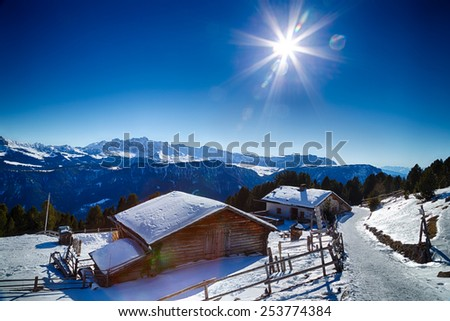 Alpine chalet surrounded by a fence in the snow in front of a panorama of snowy peaks on a bright sunny day in winter on Dolomites Alps - stock photo