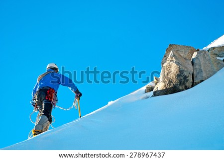 Alpine climber balances on the ice snowfield