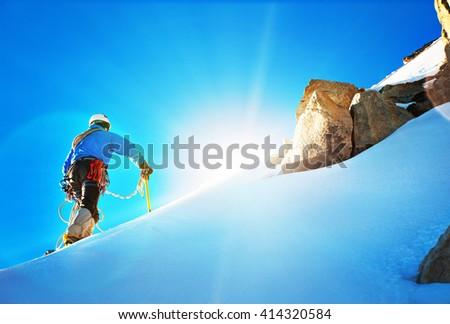 Alpine climber balances on the ice snowfield - stock photo