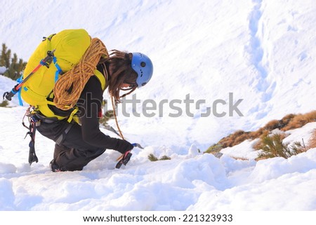 Alpine climber carries the rope on backpack on snowy terrain
