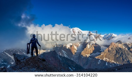 Alpine Climber Reached Summit Silhouette Man Staying on Top of Rock Cliff Holding Climbing Gear Stormy Clouds and Peaks Illuminated bright Morning Sun