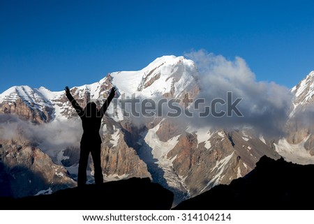Alpine Climber Reached Summit Silhouette Woman Staying on Top of Rock Cliff Triumphantly  Hands Raised Stormy Clouds and Peaks Illuminated bright Morning Sun - stock photo