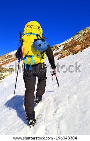Alpine climber using an ice axe while ascending the mountains in winter - stock photo