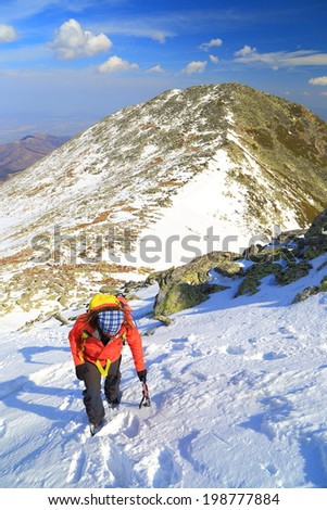 Alpine climber using the ice axe while ascending steep snow - stock photo