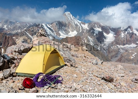 Alpine Climbers Camp in Mountains Small Yellow Tent Climbing Gear Rope Ice Axe Red Helmet Rocky Wild Terrain Majestic Peak Range View Blue Sky Clouds - stock photo