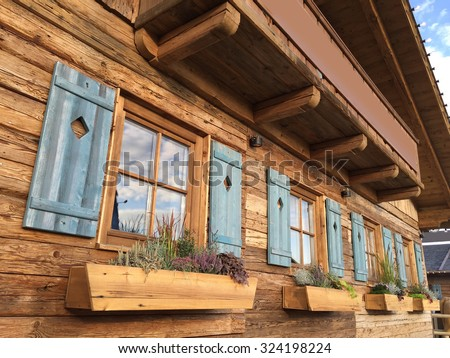 alpine cottage with blue shutters - stock photo
