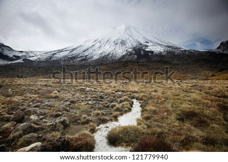 Alpine crossing, with river streaming towards the Mount Ngauruhoe. - stock photo