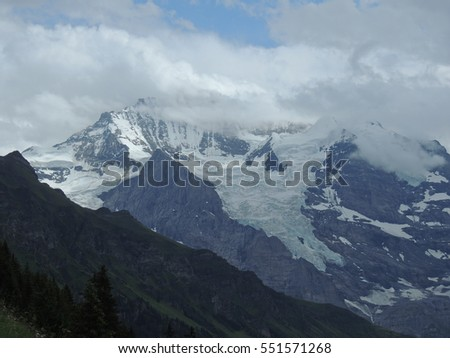 Alpine glacier with mountain peak hidden in the clouds
