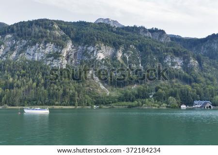 Alpine lake Mondsee autumn landscape with motor boat and boathouse, Austria - stock photo