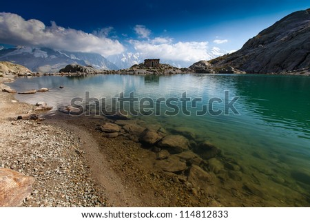 Alpine lake reflection and shelter cabin in the French Alps in summer