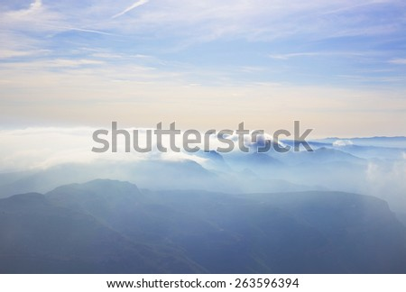 alpine landscape with peaks covered by clouds - stock photo