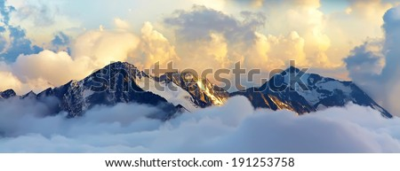 alpine landscape with peaks covered by snow and clouds. banner. panorama - stock photo