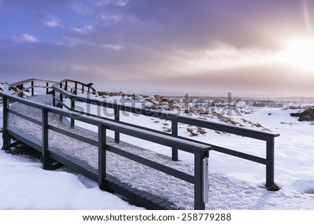 Alpine landscape with peaks covered by snow and clouds in panoramic view - stock photo