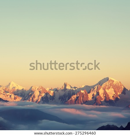 alpine landscape with peaks covered by snow and clouds. natural mountain background. vintage toning and retro stylization - stock photo