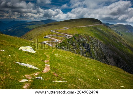 Alpine landscape with winding road and hiking trail in mountains - stock photo