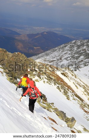 Alpine landscape with winter climbers descending a snow covered ridge in overcast day - stock photo
