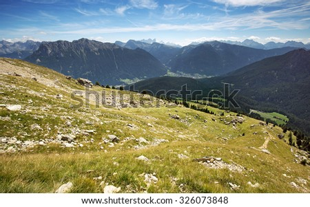 alpine meadow with panoramic view of the Dolomites - stock photo
