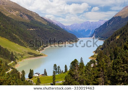 Alpine panorama. Mountain lake surrounded by pine forest and road serpentine in summer cloudy day.