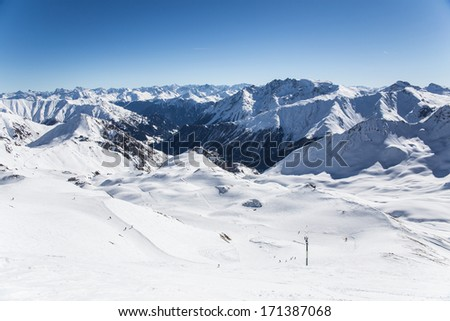 Alpine panorama showing snow covered mountains and a cloudy dramatic sky. - stock photo