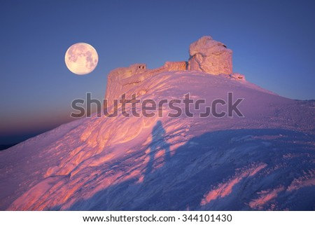 Alpine ridge Montenegro - stands on the slopes of the Ukrainian Carpathians ancient observatory , against a background of deep snow peaks and bitter cold strong wind waiting climber - extremals - stock photo