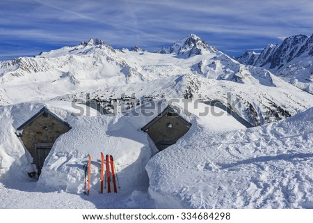 Alpine scenery with snow covered houses and ski - stock photo