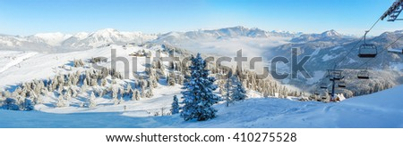 Alpine ski slope mountain winter panorama with ski lift,skiers and snow covered forest. - stock photo
