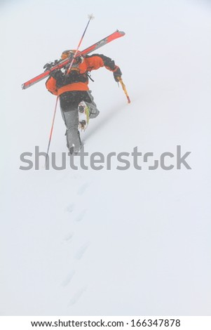 Alpine skier ascending snowy slope in bad weather - stock photo
