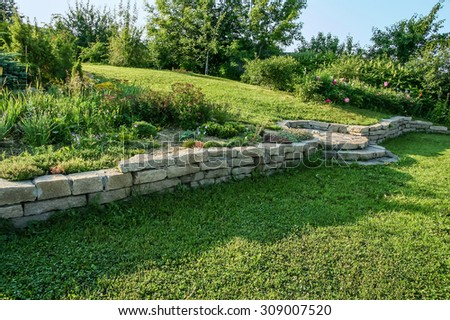 Alpine slide and retaining wall on a green slope in a landscaped garden in the morning sun