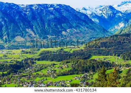 Alpine town situated in the valley of the mountains in the morning sun on a background of snow-covered peaks.