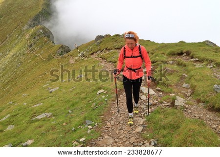 Alpine trail and fit woman hiker walking above the clouds